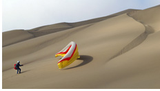 Kiting up a paraglider to the take-off at inland mountain dunes - Barefoot Dunes, Iquique, Atacama Desert, Chile